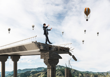 Businessman walking blindfolded on concrete bridge with huge gap as symbol of hidden threats and risks. Flying balloons and nature view on background. 3D rendering. 스톡 콘텐츠