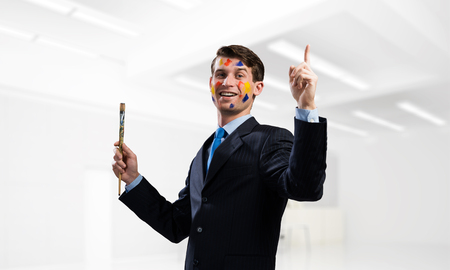Conceptual image of young and successful businessman in black suit holding paintbrush in hand and smiling while standing inside modern bright office. 스톡 콘텐츠