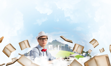 Young man writer in hat and eyeglasses using typing machine while sitting at the table among flying books with floating city and cloudy skyscape on background.