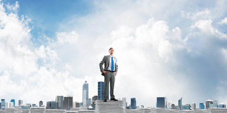 Confident businessman in suit standing on pile of documents with cityscape on background. Mixed media.