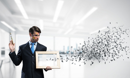 Horizontal shot of young and successful businessman in black suit holding paintbrush in hand and smiling while standing with flying letters inside modern bright office. 스톡 콘텐츠