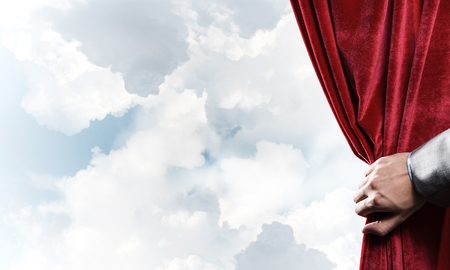 Human hand opens red velvet curtain on blue sky background Stock Photo - 117314481