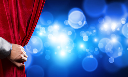 Close up of businessman hand open red velvet curtain of stage Stock fotó