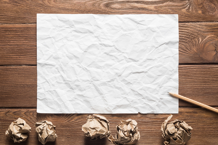 Close up of sheet of white paper and pencil on wooden table Stock Photo - 117314523
