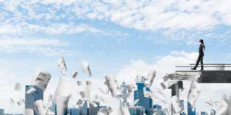Businessman walking blindfolded among flying papers on concrete bridge with huge gap as symbol of hidden threats and risks. Cityscape view on background. 3D rendering. Banco de Imagens - 117314684