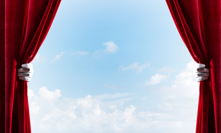 Human hand in glove opens red velvet curtain on blue sky background Stock Photo - 117314752