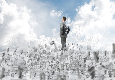 Confident businessman in suit standing on pile of documents among flying letters with cloudly skyscape on background. Mixed media. Banco de Imagens