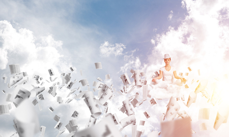 Woman in white clothing keeping eyes closed and looking concentrated while meditating among flying papers in the air with cloudy skyscape on background.