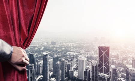 Hand of businessman opening red velvet curtain and cityscape at background Stock Photo - 117391800