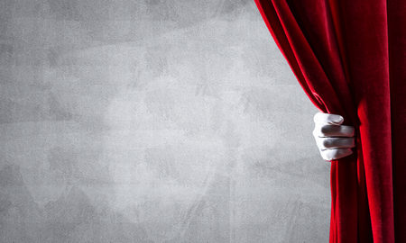 Close up of hand in white glove open red velvet curtain Stock Photo