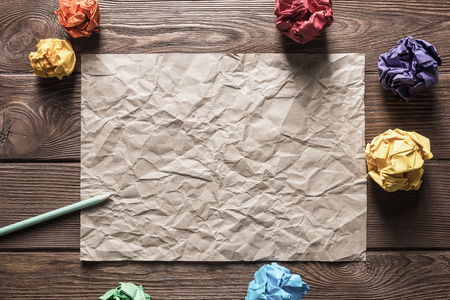 Crumpled brown paper sheet and pencil on wooden table Stock Photo - 117459183