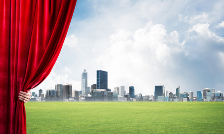Human hand opens red velvet curtain to cityscape and green meadow Stock Photo - 117455308