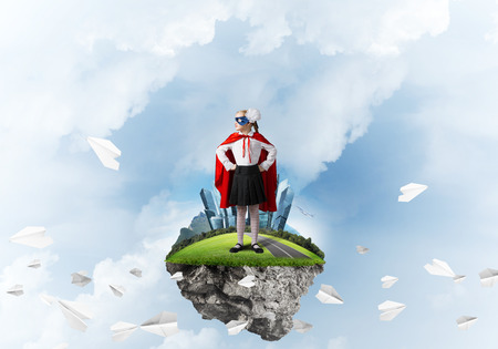 Little confident child in mask and cape on floating island plays cool superhero Imagens