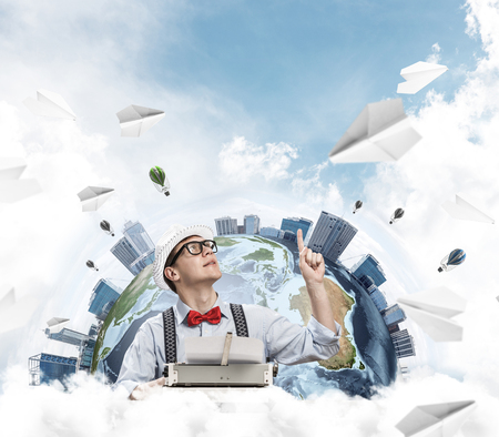 Handsome man writer in hat and eyeglasses pointing up while using typing machine at the table with flying paper planes and Earth globe among cloudy skyscape on background. Stock Photo