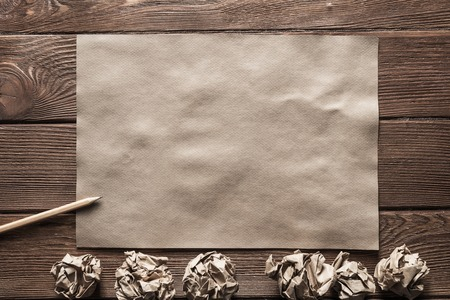 Crumpled brown paper sheet and pencil on wooden table Stock Photo - 117506244