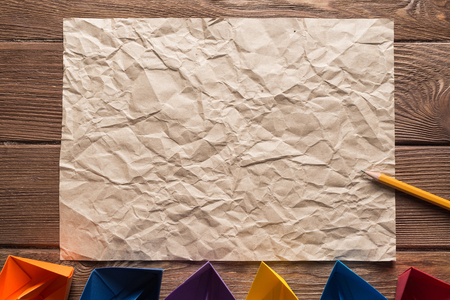 Crumpled brown paper sheet and pencil on wooden table Stock Photo - 117506246