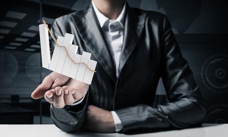 Imagen recortada del empresario en traje que presenta un gráfico de crecimiento en su mano con vista de oficina oscura sobre fondo Representación 3D. Foto de archivo