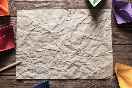 Crumpled brown paper sheet and pencil on wooden table Stock Photo - 117559953