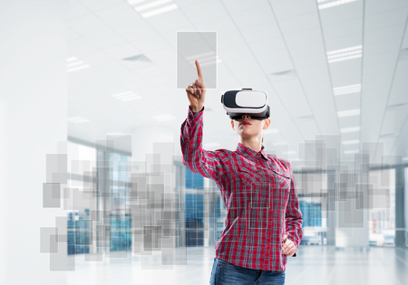 Woman in casual wearing virtual reality mask and touching icon on screen. Mixed media