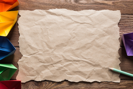 Crumpled brown paper sheet and pencil on wooden table Stock Photo - 117560168