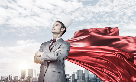 Young confident businessman wearing red cape against modern city background Reklamní fotografie