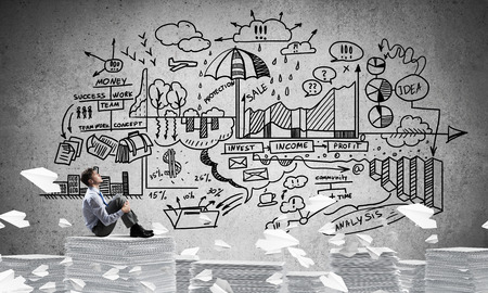 Businessman looking away while sitting on pile of documents among flying paper planes with business-plan information on background. Mixed media.