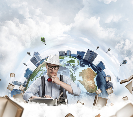 Thoughtful man writer in hat and eyeglasses looking away and touching chin while using typing machine with flying books and Earth globe among cloudy skyscape on background.