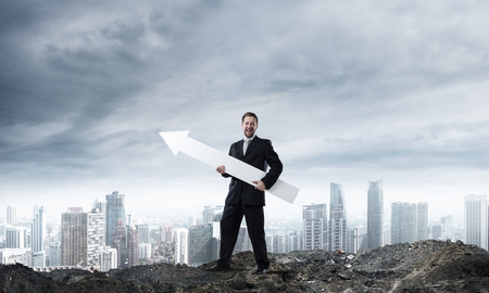 Young successful businessman in suit keeping big white arrow and pointing away while standing among ruins with cityscape view and cloudy sky on background Foto de archivo