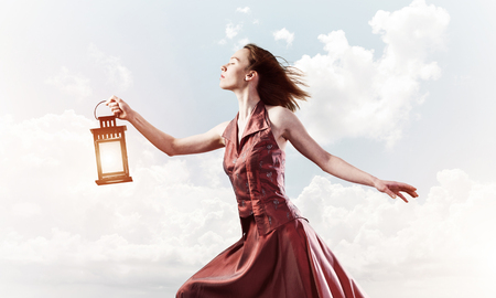 Young woman wearing dress with lantern against cloudy sky