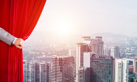 Hand of businessman opening red velvet curtain and cityscape at background Stock Photo - 118416931