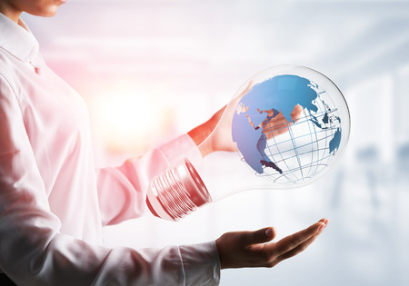 Cropped image of business woman in shirt holding lightbulb with Earth globe inside in his hands. Sunlight on office view background.