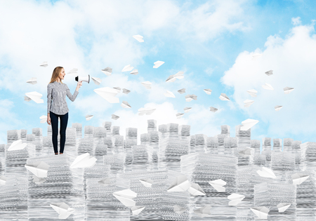 Woman in casual clothing standing on pile of documents among flying paper planes with speaker in hand with cloudly skyscape on background. Mixed media. Banco de Imagens