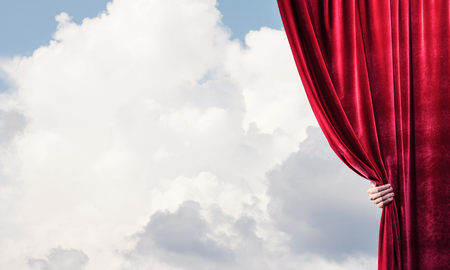 Human hand opens red velvet curtain on blue sky background Stock Photo - 118539073