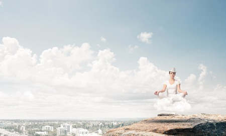 Young woman in white clothing keeping eyes closed and looking concentrated while meditating on cloud in the air with city view on background.