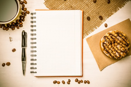 Opened notepad and cup of coffee with donut on wooden table Фото со стока
