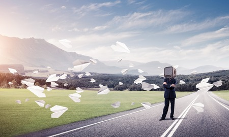 Businessman in suit with old TV instead of head keeping arms crossed while standing on the road among flying paper planes with beautiful landscape on background.