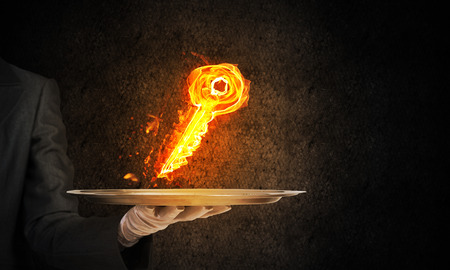 Cropped image of waitresss hand in white glove presenting flaming key symbol on metal tray with dark wall on background. Reklamní fotografie - 118686238
