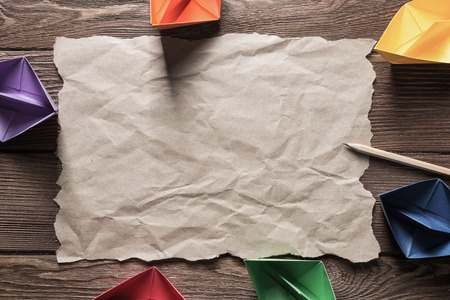 Crumpled brown paper sheet and pencil on wooden table Stock Photo - 118686512