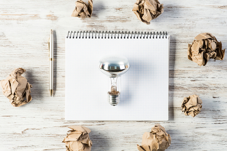 Top view of modern creative workplace with lightbulb on notepad, pen and crumpled paper balls placed on wooden table. Concept of finding of outstanding idea.