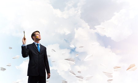 Portrait of ambitious and young business man in suit holding paintbrush in hand while standing against blue cloudy skyscape view with flying paper planes on background. Imagens - 118754013