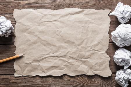 Crumpled brown paper sheet and pencil on wooden table Stock Photo - 118754028