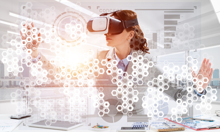 Business woman in suit using virtual reality goggles while sitting inside bright office building. Concept of modern technologies for business needs. Stock Photo