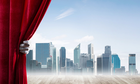 Human hand opens red velvet curtain to modern cityscape and cloudy sky Stock Photo