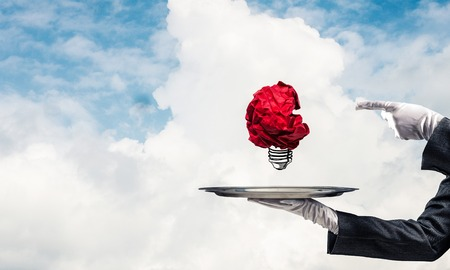 Cropped image of waitresss hand in white glove presenting crumpled paper lightbulb on metal tray and pointing on it with cloudy skyscape on background. Imagens