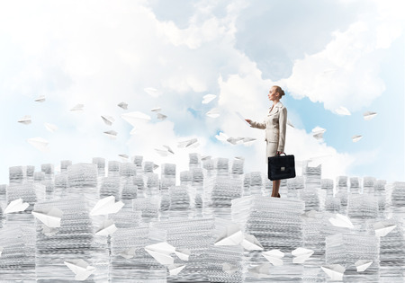 Confident business woman in suit standing on pile of documents among flying paper planes with cloudly skyscape on background. Mixed media.