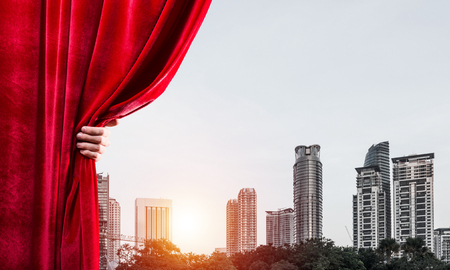 Hand of businessman opening red velvet curtain and cityscape at background