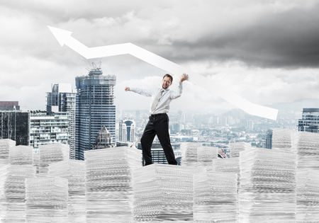 Confident young businessman in suit standing on paper columns with huge white banner in hands which pointing away and with modern cityscape view on background Banco de Imagens - 118875800