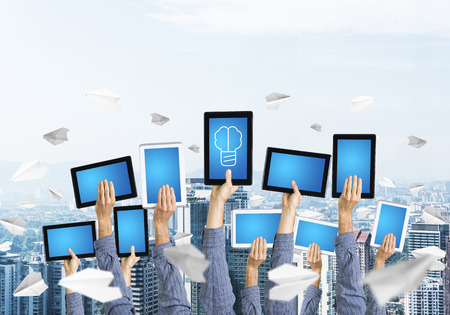 Set of tablets in male hands against modern cityscape background