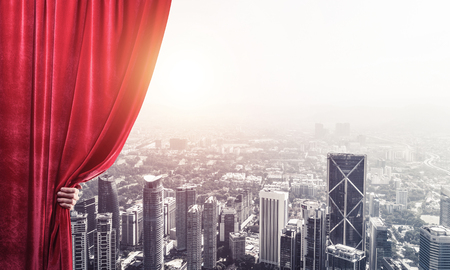 Hand of businessman opening red velvet curtain and cityscape at background Stock Photo - 118875503