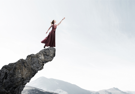 Young attractive woman relaxing in summer day standing on rock top Imagens